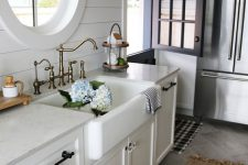 a white farmhouse kitchen with white stone countertops, a round window, vintage fixtures and a vintage sconce is a chic space