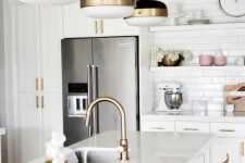 a white kitchen with shaker cabinets, a kitchen island with tall stools, black and brass pendant lamps, brass fixtures and stools with brass framing