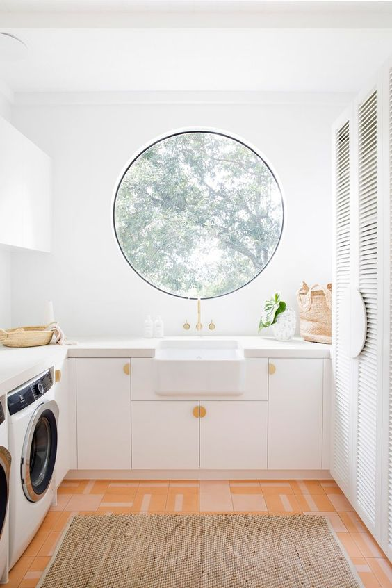 a white lanudry with shutter wardrobes, a round window, several washing machines and neutral cabinetry is amazing