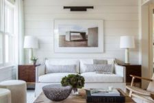 a white living room with planked walls, wooden beams, white seating furniture, a wooden slab coffee table and a bold artwork