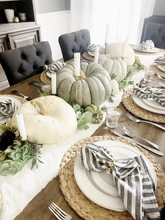 a white runner, heirloom pumpkins and candles, greenery, succulents, woven placemats, striped napkins