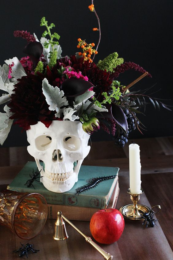 a white skull vase with deep purple blooms, pale leaves, burgundy flowers and berries is a bold and statement-like idea for Halloween