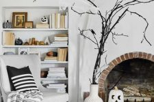 a white vase with black branches and blackbirds, a black and a white pumpkin, black and white pumpkins on the shelves