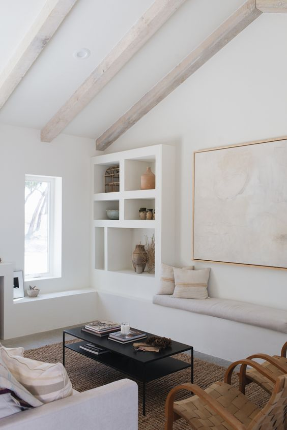 a whitewashed living room with whitewashed wooden beams, a built-in bench and shelves, a neutral sofa, woven chairs and a black coffee table