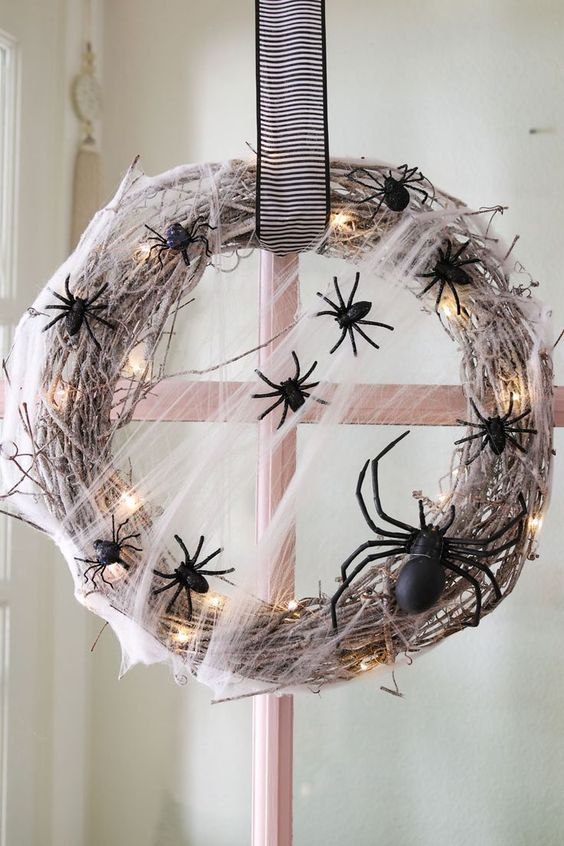 a whitewashed vine Halloween wreath with lights and spiders plus a black and white striped ribbon is a fresh take on classics