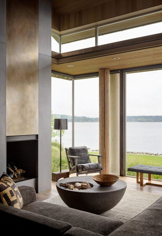 an all-natural living room with a fireplace with a gold cover, a black sectional, glazed walls for amazing views and clerestory windows for more light