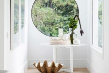 an all-white entryway with a porthole window, a white console table and bold blooms and a white bench and vase