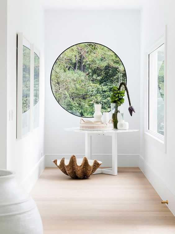 an all white entryway with a porthole window, a white console table and bold blooms and a white bench and vase