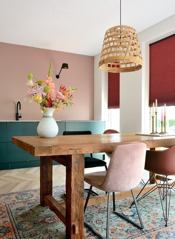 an eclectic dining room combined with a kitchen, dark green sleek cabinetry, a wooden dining table, mismatching chairs and woven pendant lamp
