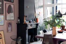 an eclectic dining room with a pink accent wall, a black fireplace, a purple dining table, dark chairs, a cool gallery wall and pendant lamps
