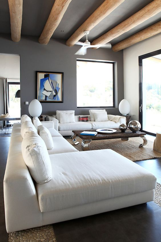 an eclectic living room with concrete walls and a ceiling, light-stained wooden beams, a white sectional, a low coffee table and large windows