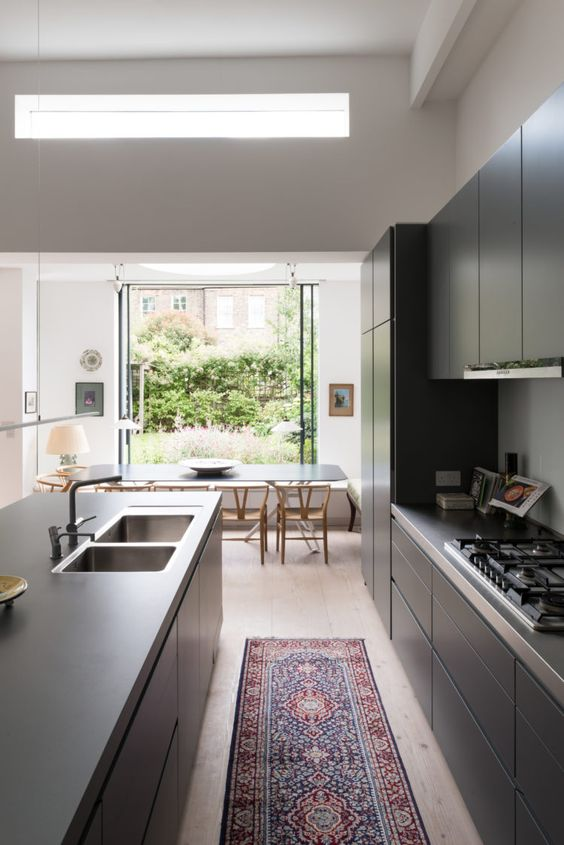 an eclectic space with black sleek furniture, light-stained chairs, a bright rug, glass doors opened to the garden and a clerestory window for more light in the kitchen