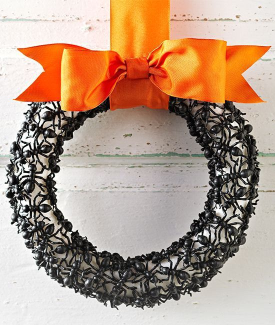 an elegant Halloween wreath covered with plastic ants, with a black orange ribbon bow is a scary and bold idea