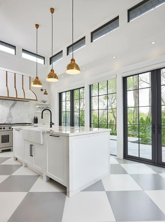 an elegant art deco kitchen in black, grey, white and gold, with a glazed wall and doors, with clerestory windows to bring more light to the double-height space