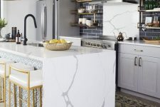 an elegant grey kitchen with shaker cabinets, black skinny tiles, a kitchen island with a waterfall countertop, brass lamps, stools and shelves