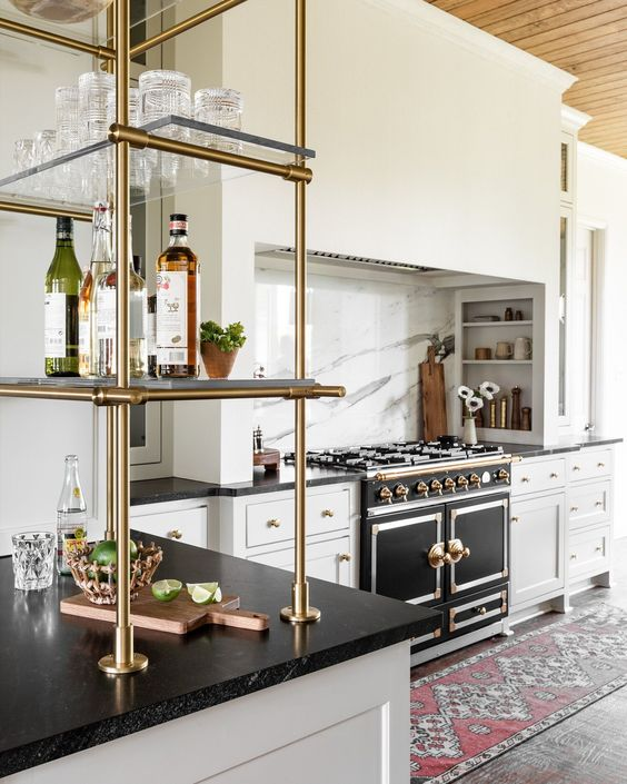 an elegant kitchen with neutral cabinets, a vintage black and brass cooker, a brass shelf and black countertops is an amazing idea
