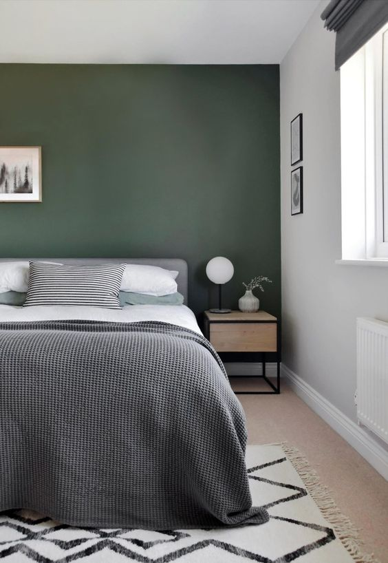 an elegant modern bedroom with a dark green accent wall, a grey upholstered bed, plywood nightstands and pretty artworks