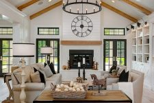 an elegant neutral living room with light-stained wooden beams, a fireplace, neutral leather seating furnitur,e a wooden console and a matching mantel