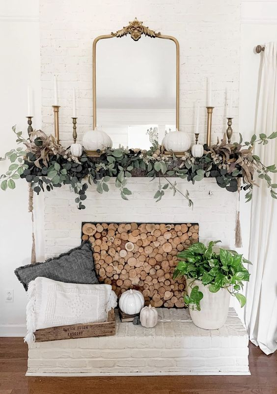 an elegant rustic fall mantel with greenery, white pumpkins, brass candlesticks and a mirror, a wood slice screen in the fireplace is chic
