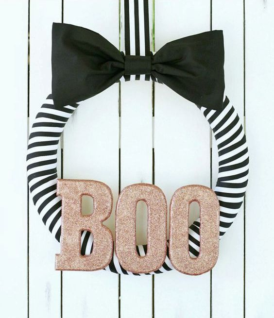 an elegant striped black and white Halloween wreath with a black bow and glitter letters is a very chic idea