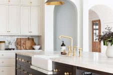 an elegant white kitchen with a chocolate brown kitchen island, brass fixtures and knobs, grey pendant lamps with brass inner is amazing