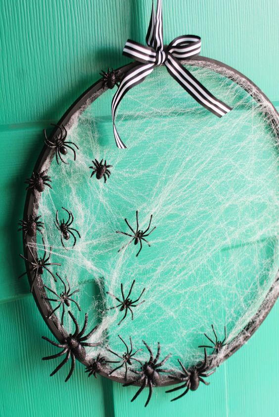 an embroidery hoop spiderweb wreath with black spiders and a striped ribbon bow is a chic and cute solution for Halloween