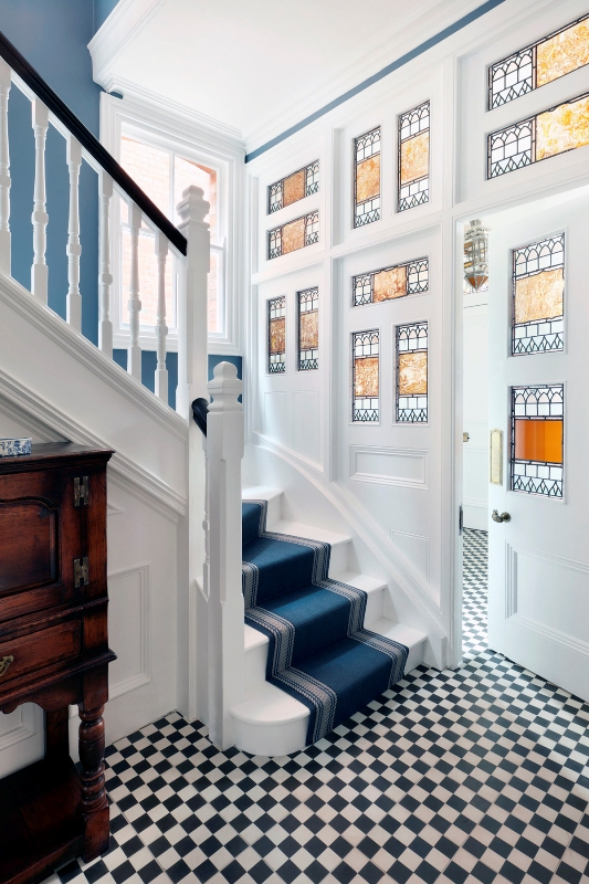 an entryway with stained glass sidelights and the door, blue walls and a checked black and white floor