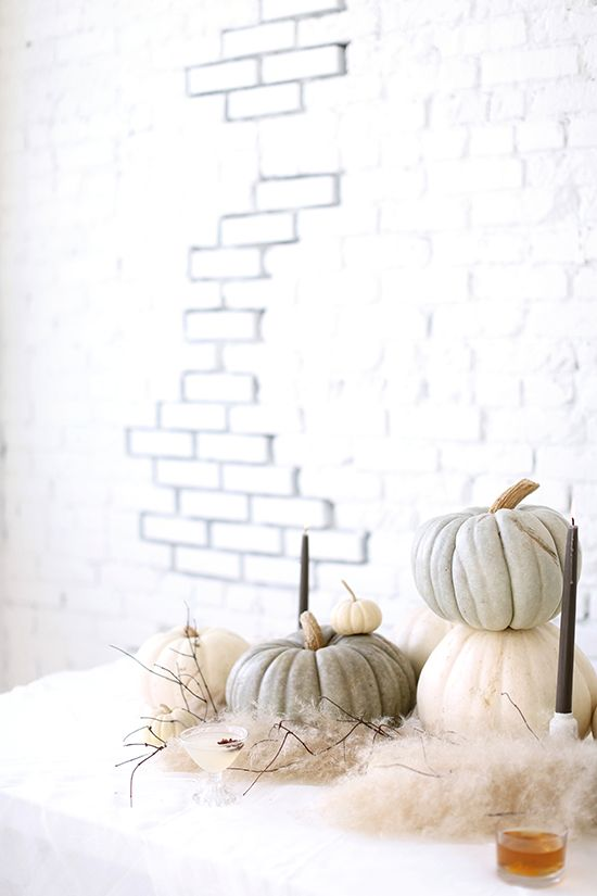 an ethereal Halloween display with naturally colored pumpkins, faux fur and candles plus branches