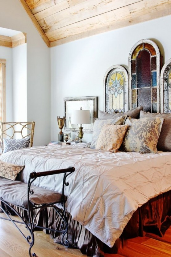 an exquisite bedroom done with vintage wrought furniture, a bed with various chic bedding and stained glass panel headboard for more chic