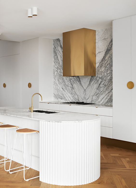 an exquisite white kitchen with ribbed cabinets and a curved kitchen island, white stone countertops and a backsplash, brass fixtures and a hood