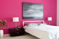 an extra bold bedroom with a hot pink accent wall, a metal bed with white bedding, black nightstands with table lamps and a moody artwork