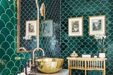 an eye-catchy bathroom with green fishscale tiles, a white vanity and appliances, a rattan table, a mirror in a brass frame and a brass bowl sink