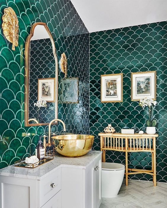 an eye catchy bathroom with green fishscale tiles, a white vanity and appliances, a rattan table, a mirror in a brass frame and a brass bowl sink