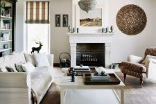 an inviting white living room with a vintage hearth in the fireplace, wooden beams, neutral vintage furniture and a black bookcase plus a metal chandelier