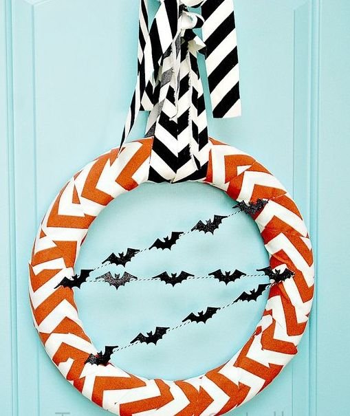 an orange and white chevron wreath with black bat buntings and a matching chevron ribbon on top is a cool and easy idea for Halloween