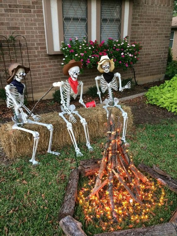an outdoor Halloween scene with skeletons sitting around the fire made of branches and lights is a cool idea for your outdoor space