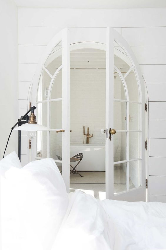 arched white French doors separating an all white bedroom and its small en suite bathroom look gorgeous and beautiful