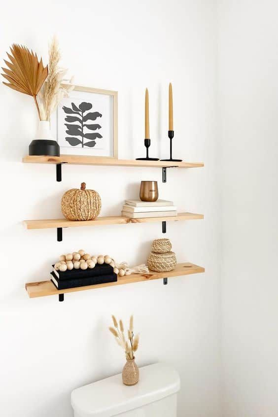 bathroom open shelving with cool fall styling - a color block vase with pampas grass and a frond, candles, a jute pumpkin and wooden beads