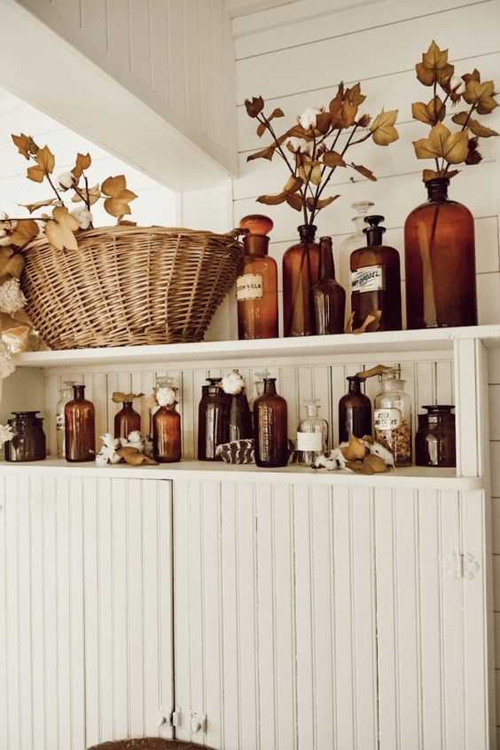 bathroom shelves with amber bottles, fall leaves, cotton and dried herbs will bring a fall spirit to the space
