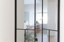black frame double-height interior glass doors with an additional vertical detail add a dramatic touch to the neutral spaces