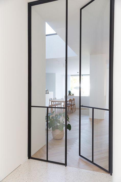 black frame double height interior glass doors with an additional vertical detail add a dramatic touch to the neutral spaces