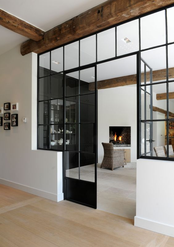 black framed French doors paired with matching windows for connecting the spaces with each other and providing both of them with natural light