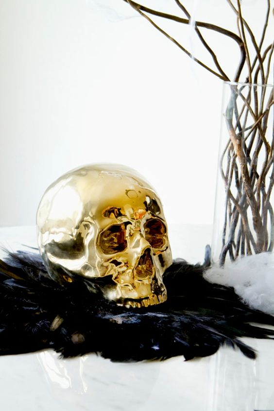 bold Halloween decor with black feathers, a gilded skull, branches in a vase is a chic and beautiful idea for glam Halloween