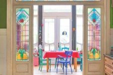 bold stained glass sidelights and doors plus colorful furniture and decor that echo with them for a bright and cool look