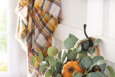 bright faux pumpkins, a pumpkin and greenery in a basket, a plaid blanket will easily cozy up your bathroom for the fall