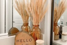 cozy and simple fall bathroom decor – a wood slice, an amber jar with wheat is amazing to style your bathroom for the fall
