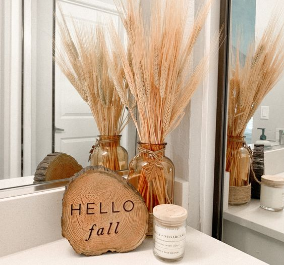 cozy and simple fall bathroom decor - a wood slice, an amber jar with wheat is amazing to style your bathroom for the fall