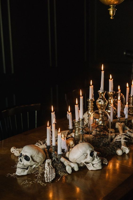 creepy and chic Halloween decor of skulls, bones, moss and candles in refined vintage candlesticks looks stylish and very elegant