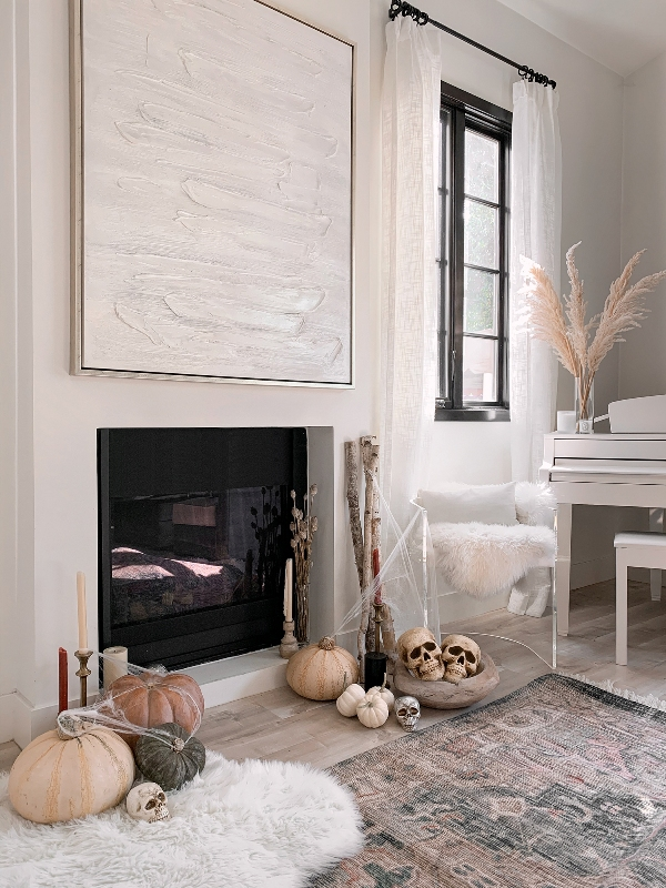 elegant modern Halloween styling with skulls in a bowl, some small and large natural pumpkins, candles and spiderweb