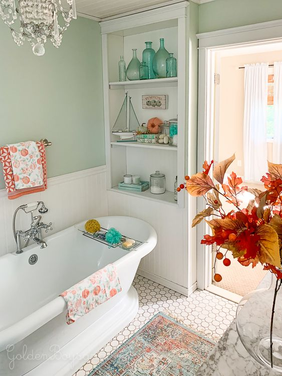 fall coastal bathroom decor with bright textiles, pumpkins and aqua-colored bottles plus a bold arrangement of leaves and berries